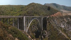 Tiro ancho escénico del fondo de los coches que se mueven a través del puente icónico de la cala de Bixby sobre la carretera 1 en almacen de video
