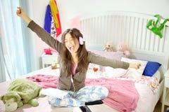 Tiro ancho sonriente de la música del canto hispánico feliz lindo de la muchacha que escucha Imagenes de archivo