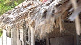 Tiro ao longo do telhado cobrido com sapê com uma rede de pesca Degradado de mar filipino Construção abandonada na ilha vídeos de arquivo