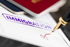 Tiro ascendente aprobado, cercano del uso de la inmigración de una forma, pasaportes y pluma fotos de archivo libres de regalías