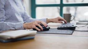 Tiro ascendente cercano de la mano de la mujer que mecanografía en el teclado del ordenador portátil y que usa el ratón del orden almacen de metraje de vídeo