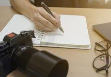Tiro ascendente cercano de la mano que está escribiendo la pluma en el cuaderno Hora laborable imagen de archivo