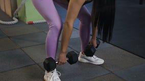 Tiro ascendente cercano de la mujer apta atractiva que se pone en cuclillas con pesas de gimnasia en el gimnasio almacen de metraje de vídeo
