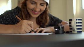 Tiro ascendente cercano de la mujer joven en una caligrafía del sombrero de la Navidad que escribe en un papel usando poner letra metrajes