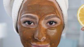 Tiro ascendente cercano de la mujer linda que presenta con la mitad dos del limón en ojos con la máscara en la cara metrajes