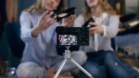 Tiro ascendente cercano de la pantalla de la cámara con el blog video de registración sobre belleza y maquillaje a partir de la m almacen de video