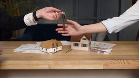 Tiro ascendente cercano de las manos femeninas del agente inmobiliario que dan llave a los clientes femeninos almacen de video