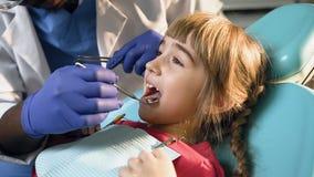 Tiro ascendente cercano de las manos masculinas del dentista que comprueban los dientes de la niña almacen de video