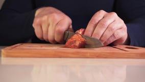 Tiro ascendente cercano de las manos de un hombre que cortan la carne cruda en una tabla de cortar metrajes
