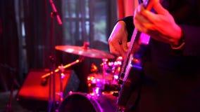 Tiro ascendente cercano de los hombres que tocan la guitarra baja blanca en etapa en la noche almacen de metraje de vídeo