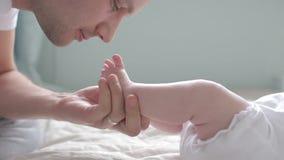 Tiro ascendente cercano de los pies que se besan del padre del bebé almacen de video