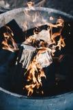 Tiro ascendente cercano de pedazos de quema de madera con el fuego en un pote grande imagen de archivo
