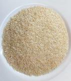 Tiro ascendente cercano de un montón del arroz crudo en una placa blanca imagenes de archivo