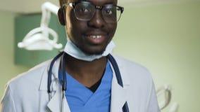 Tiro ascendente cercano del doctor africano joven en la oficina del hospital metrajes