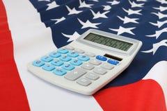 Tiro ascendente cercano del estudio de la bandera nacional rizada con la calculadora en ella - los Estados Unidos de América Fotos de archivo libres de regalías