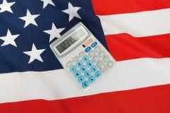 Tiro ascendente cercano del estudio de la bandera nacional rizada con la calculadora sobre ella - los Estados Unidos de América Imagenes de archivo