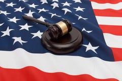 Tiro ascendente cercano del estudio de un mazo del juez sobre la bandera de los Estados Unidos de América imagen de archivo
