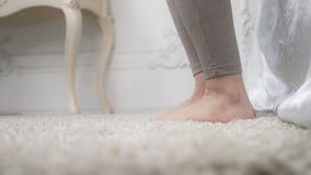 Tiro ascendente cercano del primer paso de la mañana de la mujer de la cama a la moqueta con los pies descubiertos en su dormitor almacen de video