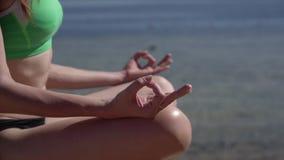 Tiro ascendente próximo da ioga da prática na praia do oceano filme