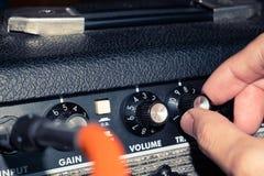 Tiro ascendente próximo da mão que ajusta o botão de controle do amplificador da guitarra imagens de stock