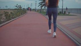 Tiro ascendente próximo da mulher desportiva com a figura magro que corre fora na vista crepuscular, traseira vídeos de arquivo