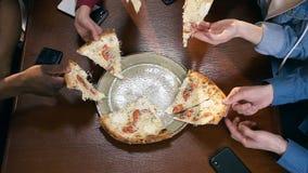 Tiro ascendente próximo das mãos fêmeas e masculinas que tomam a parte de pizza video estoque