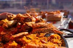 Tiro ascendente próximo de camarões e de arroz do paella no mercado fotografia de stock royalty free