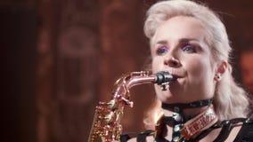 Tiro ascendente próximo de um saxofonista fêmea com a composição brilhante que executa uma música video estoque