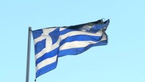 Tiro ascendente próximo de um voo grego da bandeira no vento vídeos de arquivo