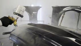 Tiro ascendente próximo do trabalhador que aplica a pintura na peça do carro no serviço do carro vídeos de arquivo