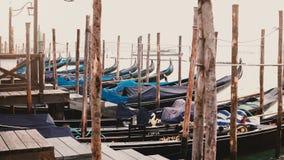Tiro atmosférico de las góndolas vacías tradicionales hermosas que oscilan en las ondas en el embarcadero de madera antiguo en Ve almacen de metraje de vídeo