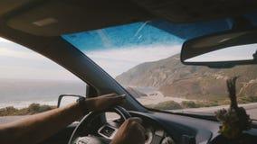 Tiro atmosférico del POV del hombre que conduce a lo largo del camino soleado increíble de la costa del océano con Mountain View  almacen de video