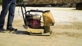 Tiro bajo de la superficie de presión de la arena del hombre con el compresor vibratorio de la placa almacen de video