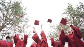 Tiro bajo de los graduados felices que lanzan birretes en aire, riendo y celebrando la graduación en campus de la universidad almacen de metraje de vídeo