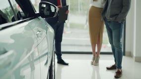 Tiro bajo de los pares jovenes de la gente próspera que compran el nuevo coche en la representación y que hablan con el encargado almacen de metraje de vídeo