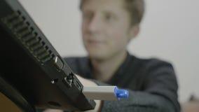 Tiro bajo de un muchacho rubio joven del estudiante que inserta un palillo de memoria USB en su ordenador portátil para copiar el metrajes