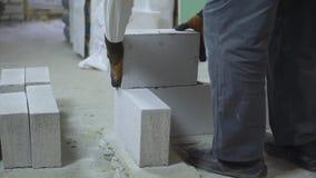 Tiro bajo del constructor que pone el bloque de cemento aireado almacen de video