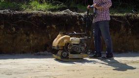 Tiro bajo del trabajador que usa el pisón vibrante en superficie de la arena almacen de metraje de vídeo