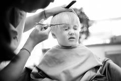 Tiro blanco y negro del muchacho del preescolar que consigue corte de pelo Foto de archivo