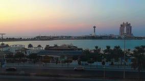 Tiro bonito do corniche da cidade de Abu Dhabi e da praia no por do sol - Marina Mall filme