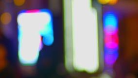 Tiro borrado das silhuetas de pedestres de passeio em nivelar o fundo colorido das luzes da cidade vídeos de arquivo