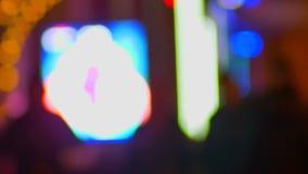 Tiro borroso de siluetas de peatones fastly que caminan en la igualación del fondo multicolor de las luces de la ciudad almacen de metraje de vídeo