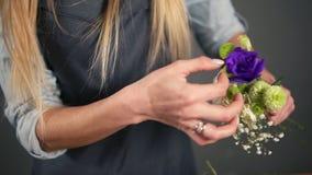 Tiro a cámara lenta de manos del artista floral de sexo femenino rubio profesional que arregla el ramo hermoso en la floristería almacen de video