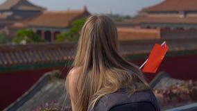 Tiro a cámara lenta de Steadicam de un bloger del viaje de la mujer joven que visita la ciudad Prohibida - palacio antiguo del em almacen de video