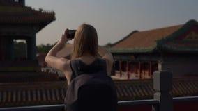 Tiro a cámara lenta de Steadicam de un bloger del viaje de la mujer joven que visita la ciudad Prohibida - palacio antiguo del em almacen de metraje de vídeo