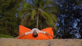 Tiro a cámara lenta de un hombre joven que se divierte en un sofá inflable en una playa hermosa metrajes