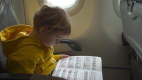 Tiro a cámara lenta de un muchacho en chaqueta amarilla a bordo de un aeroplano que lee una instrucción de seguridad almacen de metraje de vídeo