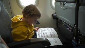 Tiro a cámara lenta de un muchacho en chaqueta amarilla a bordo de un aeroplano que lee una instrucción de seguridad almacen de video