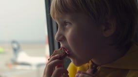 Tiro a cámara lenta de un muchacho joven en una chaqueta amarilla que come una galleta sittting delante de una ventana grande en  almacen de metraje de vídeo