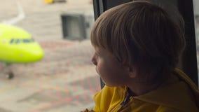 Tiro a cámara lenta de un muchacho joven en una chaqueta amarilla que come una galleta sittting delante de una ventana grande en  metrajes